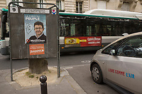 France. Ile de France. Paris. Partially torn campaign poster of French presidential election candidate<br /> Jean-Luc M&eacute;lenchon for the leftist political movement &quot;Front de Gauche&quot; (FG). A public bus rides on the road. A parked Bollore BlueCar Electric car used for Autolib' car sharing service with written words on the side door &quot; Free as the air&quot;. 22.04.17 &copy; 2017 Didier Ruef