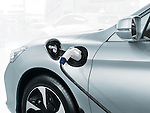 Plug-in electric car with a power cord plugged into a power socket, recharging batteries at a charging station