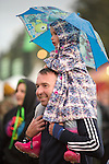 Electric Fields music festival at Drumlanrig Castle near Dumfries Scotland, girl child on fathers shoulders with umbrella
