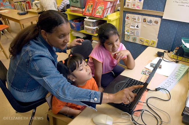 Oakland CA Special education teacher helping developmentally disabled primary school students learn via computer in class  MR