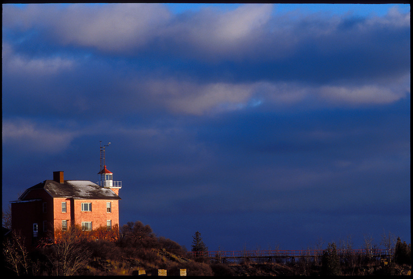 MARQUETTE LIGHTHOUSE AT DAWN UNDER LAKE SUPERIOR STORM CLOUDS IN MARQUETTE MICHIGAN.