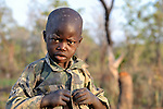 A boy gets dressed early in the morning in the Southern Sudan village of Kupera.