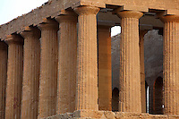 Detail of columns, Temple of Concord, 5th century BC,  Agrigento, Sicily, Italy,  pictured on September 11, 2009, in the evening. Well preserved owing to its 6th century AD conversion to a church, the Temple of Concord is a typical example of optical correction whose tapering columns create the illusion of a perfectly aligned building. Its frieze consists of alternating triglyphs and metopes, and the pediment is undecorated. The Valley of the Temples is a UNESCO World Heritage Site. Picture by Manuel Cohen.