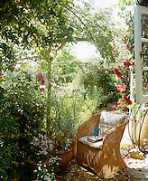 A comfortable wicker chair is situated in a shady part of the brick terrace under the rose-covered pergola