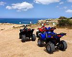 Stock photo of Three PGO X-Rider all-terrain vehicles standing near a coastline under blue summer sky Cape Gkreko Cyprus 2007 Travel journey summer vacation bike rental tourism recreational concept Horizontal
