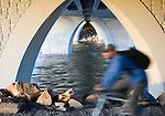 A bike rider passes under the Orange Street bridge on the riverfront trail in Missoula, Montana