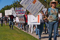 Occupy Orange County, Irvine marchers walk down the sidewalk of Alton in Irvine, CA as a part of their Saturday protest against banks.  Many signs are visible.