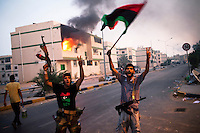 Rebel fighters celebrateas they walk past a burning apartment building after spending the day chasing Gaddafi loyalist snipers in the neighbourhood of Abu Salim. After a six month revolution, rebel forces finally managed to break into Tripoli and have taken control of Bab al-Aziziyah, Col Gaddafi's compound and residence. Few remain that are loyal to Gaddafi in the city; it is seeming that the 42 year regime has come to an end. Gaddafi is currently on the run..
