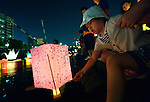 A child sets a floating candle lantern on the river on August 6, 2015, in Hiroshima, Japan. The lanterns, thousands of which were launched on the 70th anniversary of the atomic bombing of the city, carried handmade messages and drawings, conveying each person's prayers for peace and comfort for the victims of the violence.
