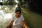 A Mayan couple paddles upstream in their dugout canoe, near their traditional village, Crique Sarco in Southern Belize.....Man paddling is a ranger in Sarstoon-Temash National Park, employed by SATIM - a foundation to preserve native culture and the natural environment in the park.