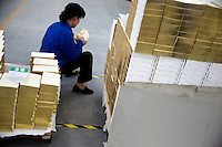 "An Amity Printing Company employee examines the quality of newly-printed gold-edged Bibles in the Amity Printing Company's new printing facility in Nanjing, China....On May 18, 2008, the Amity Printing Company in Nanjing, Jiangsu Province, China, inaugurated its new printing facility in southern Nanjing.  The facility doubles the printing capacity of the company, now up to 12 million Bibles produced in a year, making Amity Printing Company the largest producer of Bibles in the world.  The company, in cooperation with the international organization the United Bible Societies, produces Bibles for both domestic Chinese use and international distribution.  The company's Bibles are printed in Chinese and many other languages.  Within China, the Bibles are distributed both to registered and unregistered Christians who worship in illegal ""house churches."""