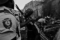 Port Au Prince, Haiti, Jan 25 2010.A prisoner pleads his innocence...Everyday since the disaster, thousands of inpoverished inhabitants try to recover valuable goods in the ruins of downtown Port-au-Prince; sometimes it turns into downright looting of warehouse or shops; the police acts vigorously against the looters but it is sometimes difficult to draw the line between 'honnest' recovery and looting..