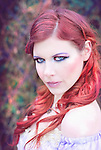 A smirking young woman with bright red hair and fancy attire looking at camera