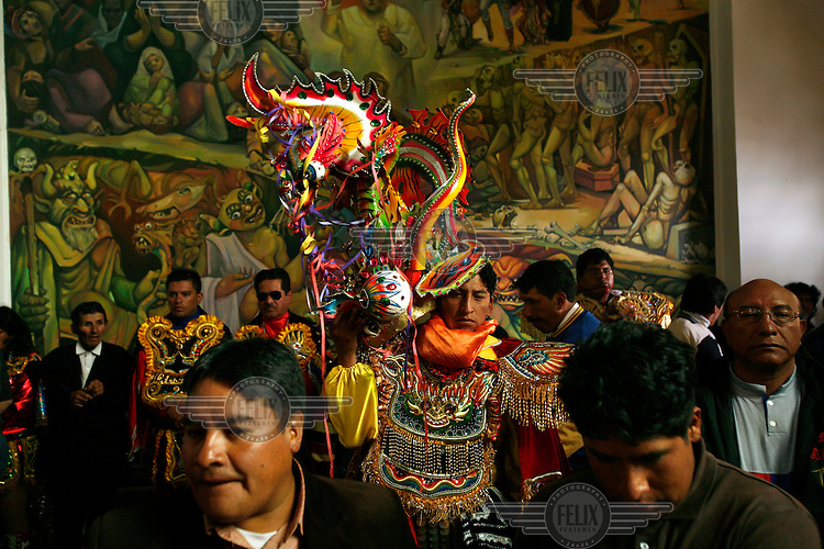 A man with an elaborate costume arrives at a church at the Carnaval de Oruro. During the fiesta many people sacrifice llamas and give offerings such as coca leaves and cigarettes to show their dedication to the Devil, a Virgin, Pachamama or Mother Earth. The Devil (or Uncle) is a mythical character that protects the miners of Oruro who work in dangerous conditions hundreds of metres below the ground. During the carnival, people dress in outrageous costumes and dance for days before arriving at the Church of Socavon, where they pay their respects to a virgin. Ironically, many of the dancers wear devil costumes.