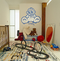 Playful wall art by Andre Charles illustrates this boy's bedroom scattered with toys and furnished with a rug by Sean Landers for Art Production Fund