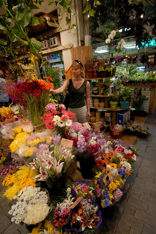 Reading Terminal Market, woman buying flowers, mod rel..Philadelphia, Pennsylvania, PA USA.  Photo copyright Lee Foster, 510-549-2202, lee@fostertravel.com, www.fostertravel.com.  Photo 225-30512