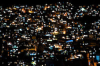 City lights seen on a steep hillside in the favela of Rocinha, Rio de Janeiro, Rio de Janeiro, Brazil, 20 February 2012. Rocinha, the largest shanty town in Brazil and one of the most developed in Latin America, has its own samba school called GRES Academicos da Rocinha. The Rocinha samba school is very loyal to its neighborhood. Throughout the year, the entire community actively participate in rehearsals, culture events and parades related to the carnival.