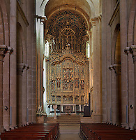 Nave with altar and altarpiece in the main chapel, in the Old Cathedral of Coimbra, or Se Velha de Coimbra, a 12th century Romanesque Roman Catholic cathedral in Coimbra, Portugal. The altarpiece, 1503, is of gilded and polychrome wood in Gothic style, was commissioned by Bishop Jorge de Almeida and made by the Flemish masters Olivier de Gante and Jean d'Ypres. The cathedral was designed by Master Robert, a French architect, with the works overseen by Master Bernard and Master Soeiro. It was reworked in the 16th century, with the addition of tiled decoration, a portal and Renaissance chapel. The city of Coimbra dates back to Roman times and was the capital of Portugal from 1131 to 1255. Its historic buildings are listed as a UNESCO World Heritage Site. Picture by Manuel Cohen