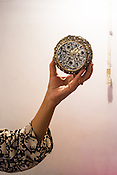 A woman holds rare and fine jewelry for a photo in Gem Palace in Jaipur, Rajasthan, India.