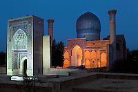 Low angle view of the Gur-Emir Mausoleum, 1404, Samarkand, Uzbekistan, seen at twilight, on July 14, 2010. Floodlighting enhances the decorative tiled archways and loggias of the domed building, whose blue colour scheme compliments the evening sky. Samarkand, a city on the Silk Road, founded as Afrosiab in the 7th century BC, is a meeting point for the world's cultures. Its most important development was in the Timurid period, 14th to 15th centuries.