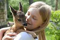 Rehkitz, Reh-Kitz, verwaistes, pflegebedürftiges Jungtier wird in menschlicher Obhut großgezogen, Kind, Mädchen hat Kitz auf dem Arm, Kitz, Tierkind, Tierbaby, Tierbabies, Europäisches Reh, Ricke, Weibchen, Capreolus capreolus, Roe Deer, Chevreuil