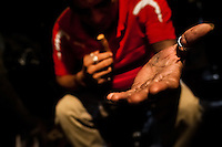 A Salvadorean 'brujo' (sorcerer) stretches out his hand towards the client before starting the tobacco reading ritual in a street fortune telling shop in San Salvador, El Salvador, 18 February 2014. Due to the strong historical tradition of using tobacco by indigenous shamen in Americas, nowadays, the reading of tobacco is one of the most most widespread methods of divination, employed by esoteric practitioners and healers in all Latin American countries. According to the shapes of burn leaves, colors of ash and smoke, burning velocity and other factors, the experienced fortune teller interprets the manifested signs in relation with the supposed future of people involved in the tobacco ritual.