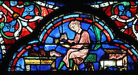 A cobbler lacing shoes, from the donor window of the shoemakers, from the Glorification of the Virgin stained glass window, 13th century, in the nave of Chartres cathedral, Eure-et-Loir, France. Chartres cathedral was built 1194-1250 and is a fine example of Gothic architecture. Most of its windows date from 1205-40 although a few earlier 12th century examples are also intact. It was declared a UNESCO World Heritage Site in 1979. Picture by Manuel Cohen