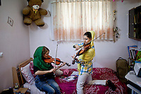 Two young women practicing the violin.