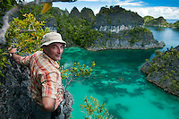 Raja Ampat Archipelago, West Papua, Indonesia, December 2010. Dutch adventurer, pioneer, and dive operator Max Ammer is the driving force behind a community tourism project.  Thousands of small islands fringed by coral reefs and blue water mangroves litter the Raja Ampat archipelago. The turquoise and blue waters are teeming with marine life that forms the livelihood for the local Papuan population. The Raja Ampat Research & Conservation Centre (RARCC) supports the locals to develop a community based, sustainable tourism project, inviting visitors to explore their islands by sea kayak and experience the culture by staying amongst the local people in traditional style homestays. Photo by Frits Meyst/Adventure4ever.com