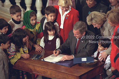 United States President George W. Bush signs the Afghan Women and Children Relief Act of 2001 at the National Museum of Women in the Arts in Washington, D.C., Wednesday, December 12, 2001..Mandatory Credit: Tina Hager - White House via CNP.