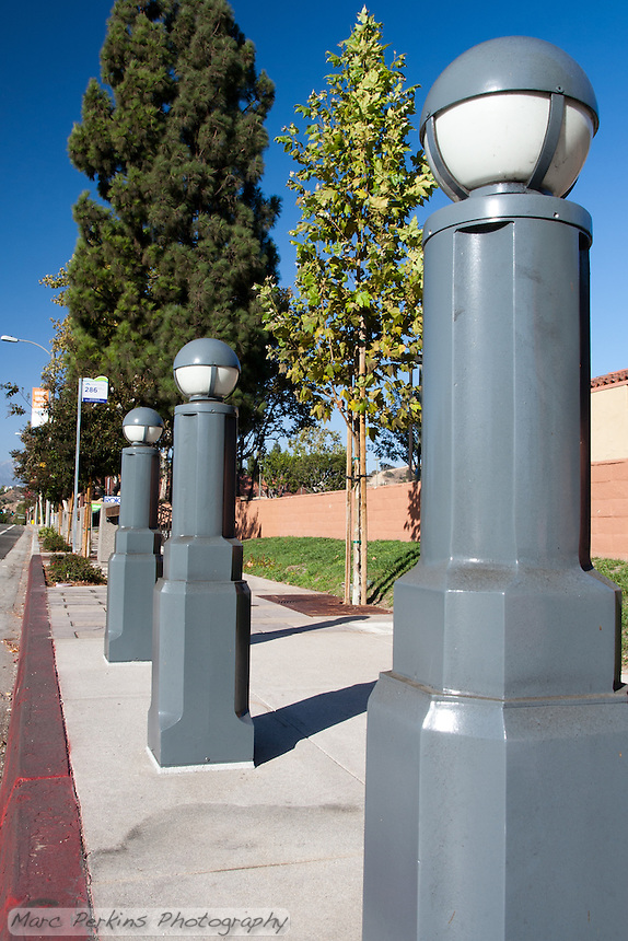 """Three blue-gray metal lights (that remind me of little soldiers in a row) stand at the bus stop on the northeastern corner of Gand and Diamond Bar.  Plenty of blue sky is visible in this wide angle shot. This was part of the 2015 rebuild of the Grand Avenue and Diamond Bar Boulevard intersection for Diamond Bar's 2015 """"Grand Avenue Beautification"""" project, landscape architecture for the project was by David Volz Design."""