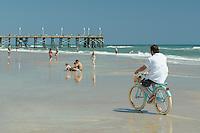 Man on bicycle on Daytona Beach, Daytona Beach Pier in background. Florida, USA