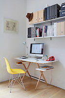 A simple home office furnishes a corner of the living room with an Achille Castiglioni desk lamp and a yellow Eames chair