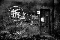 A mandarin chinese character (in white circle) spray-painted on the side of a building indicates the building will soon be demolished in Tianjin, China.  The building stands in the former site of a hutong, a traditional Chinese residential alleyway, which is being demolished to make way for the construction of modern high-rise buildings in central Tianjin, China..