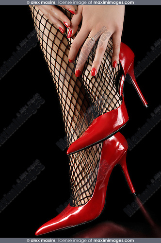 Sexy glamorous woman in fishnet stockings and red shiny stylish high heel shoes Closeup of beautiful legs