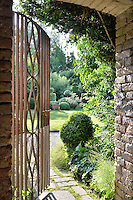 Inside a garden building with rough stone walls. An open wrought-iron gate leads to a garden beyond.