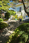 A small flagstone patio surrounded by garden offers a peaceful place to relax in this Seattle front yard.