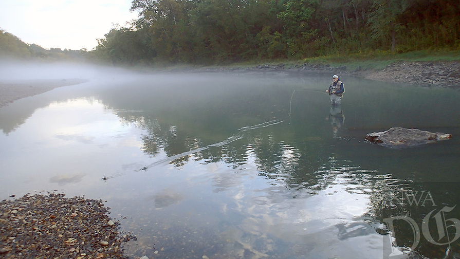 NWA Democrat-Gazette/FLIP PUTTHOFF <br /> Mist shrouds the White River below Beaver Dam many mornings, making the stream a scenic one to fish. Gary Henderson casts for trout   Oct. 8 2016 in a quiet pool.