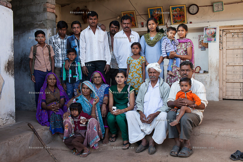 Video Volunteer videojournalist Niru J. Rathod (center, in green), 24, sits for a group portrait with an upper caste family that discriminated against her when she first met them but now respect her for the social change she has brought about in their remote village in Surendranagar, Gujarat, India on 14 December 2012. The last time Niru had come to their home, she was discriminated against and served tea in a saucer meant for lower castes. Now, after seeing the effects of her video activism, the family no longer discriminates against her. Niru, the 8th child in a family of 11 girls born to a Dalit construction worker, has been using videography for social change since 2006. She shoots and produces her own short documentaries and is a committed video activist, having conducted hundreds of village video screenings where she also speaks to thousands of men, shattering their ideas about what a woman and a Dalit can do while bringing massive changes to the communities she documents. Photo by Suzanne Lee / Marie Claire France