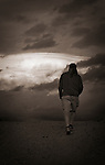 A man walks up a hill in the evening with dramatic clouds overhead.