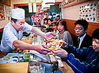 """Tokyo sushi chef serves his """"special"""" as other customers enviously gaze on."""