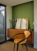 A wall mounted cabinet and a pair of prints against a green wall furnish a small hallway