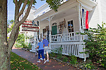 Two people walk past an antique shop in Wiscasset, Maine