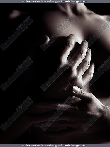 Sensual closeup of man hand covering nude woman breast, black and white abstract body parts
