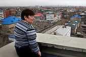 A woman sits atop a building overseeing the town of Zabaikalsk, on the Russian side of the Russian-Chinese border.