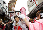 """Participants carry a portable shrine on which is mounted a 2.5 meter pink phallus in the grounds of Wakamya Hachimangu shrine during the Kanamara Festival in Kawasaki, Japan on 04 April 2010. The fertility festival, often just called the """"penis festival,"""" has been held since the early 1600s. Today, the festival also aims to promote awareness of AIDS and STDs"""