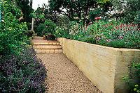 The entrance to the garden has a walled raised bead gravel path and tiled steps leading up to the house