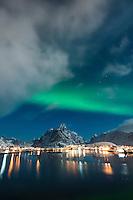 Northern lights shine in sky over Reine, Moskenesøy, Lofoten Islands, Norway