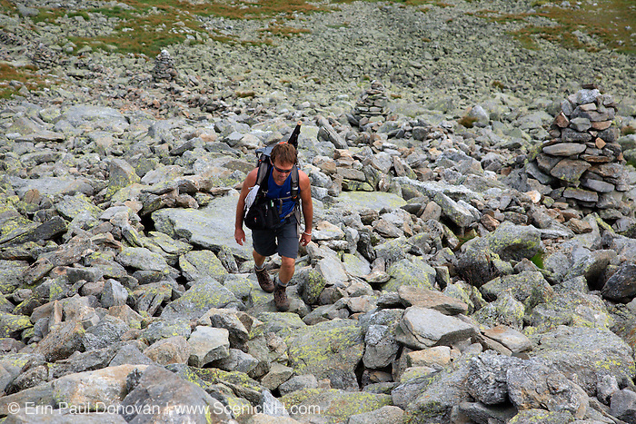 """Hiker ascending the Nelson Crag Trail over Felsenmeer barrens near the summit of Mount Washington in the White Mountains, New Hampshire. Felsenmeer barrens  are found in the alpine zone of the Presidential Range. Felsenmeer is a German word meaning """"Sea Of Rocks"""""""