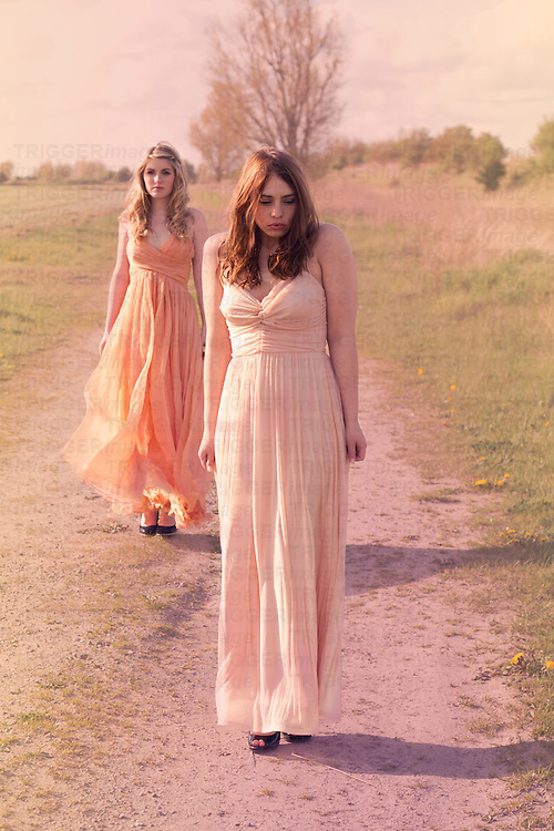 Two young women standing together in the nature wearing pastel colored dresses